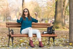 Young beautiful teenage girl sitting on the park bench and holding her hair Royalty Free Stock Photography