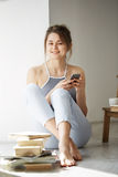 Young beautiful teenage girl surfing internet at phone smiling looking at camera sitting on floor among old books near Royalty Free Stock Image