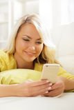 Young and beautiful teenage girl typing sms using a smartphone stock photography