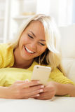 Young and beautiful teenage girl typing sms using a smartphone Royalty Free Stock Photos