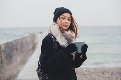 Young beautiful teenager girl drinks coffee and on the beach Royalty Free Stock Image