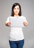Young and beautiful teenager girl holding an ipad tablet pc in h Stock Images
