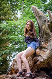 Young beautiful teenager girl with long hair in a shirt and denim shorts resting on a tree during a walk in the park Striysky in L Royalty Free Stock Photo