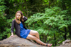 Young beautiful teenager girl with long hair in a shirt and denim shorts resting on a tree during a walk in the park Striysky in L Stock Photos