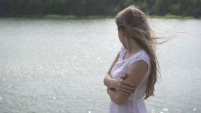Young beautiful teenager girl standing on stone near mountain lake. Close-up stock footage