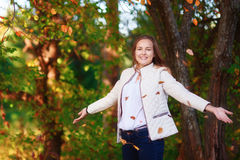 Young beautiful teenager girl tosses colorful autumn leaves in park royalty free stock images