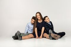 Young beautiful teenagers sitting together on the ground royalty free stock photos
