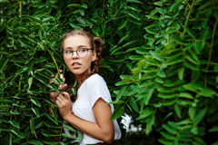 Young beautiful tender female student wearing glasses hiding in leaves. Royalty Free Stock Images