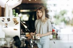 A young beautiful thin blonde with long hair,dressed in casual outfit,is cooking coffee in a modern coffee shop. Process royalty free stock photography