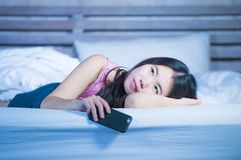 Young beautiful and thoughtful Asian Chinese woman on her 20s holding mobile phone lying on bed at night thinking looking sad and. Sweet maybe wondering or royalty free stock photography