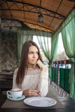Young beautiful thoughtful brunette woman waiting in cafe terrace with a cappuccino cup Royalty Free Stock Image