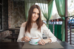 Young beautiful thoughtful brunette woman waiting in cafe terrace with a cappuccino cup Royalty Free Stock Images
