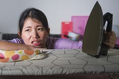 Young beautiful tired and frustrated Asian Chinese woman holding ironing stressed and upset leaning on iron board at home kitchen stock image