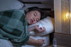 Young beautiful tired and ill Asian Korean woman lying on bed at home sick suffering cold flu and temperature covered with blanket royalty free stock images