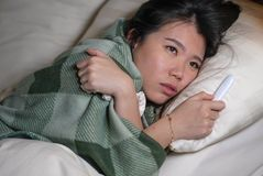 Young beautiful tired and ill Asian Korean woman lying on bed at home sick suffering cold flu and temperature covered with blanket stock photography