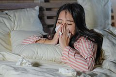 Young beautiful tired and ill Asian Korean woman lying on bed at home sick suffering cold flu and temperature covered with blanket stock images