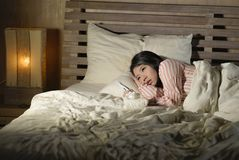 Young beautiful tired and ill Asian Korean woman lying on bed at home sick suffering cold flu and temperature feeling unwell and royalty free stock image