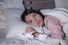 Young beautiful tired and ill Asian Korean woman lying on bed at home sick suffering cold flu and temperature feeling unwell and royalty free stock photos