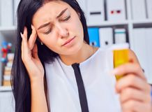 Young beautiful tired sick woman sitting in workplace in office holding bottle with pills. Female feeling bad at work. royalty free stock image