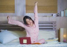 Young beautiful tired and sleepy Asian Japanese student girl stretching in bed after long hours studying late for college exam royalty free stock photography