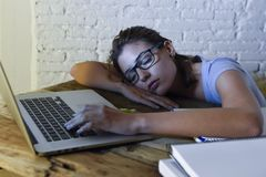 Young beautiful and tired student girl sleeping taking a nap lying on home laptop computer desk exhausted and wasted spending nigh. T studying in stress Royalty Free Stock Images