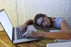 Young beautiful and tired student girl sleeping taking a nap lying on home laptop computer desk exhausted and wasted spending nigh Stock Photos