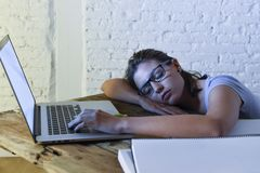 Young beautiful and tired student girl sleeping taking a nap lying on home laptop computer desk exhausted and wasted spending nigh Stock Image
