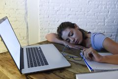 Young beautiful and tired student girl sleeping taking a nap lying on home laptop computer desk exhausted and wasted spending nigh Stock Images