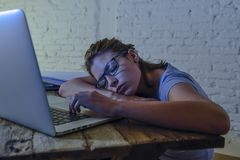 Young beautiful and tired student girl sleeping taking a nap lying on home laptop computer desk exhausted and wasted spending nigh Royalty Free Stock Photo