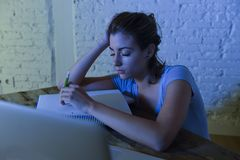 Young beautiful and tired student girl sleeping taking a nap lying on home laptop computer desk exhausted and wasted spending nigh Stock Photo