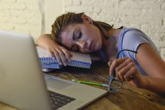 Young beautiful and tired student girl sleeping taking a nap lying on home laptop computer desk exhausted and wasted spending nigh Stock Photography