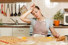 Little kid boy helps mother to cook ginger biscuit. Happy family mom and child in weekend morning at home. Relationship. The young beautiful tired woman 30-35 royalty free stock photos