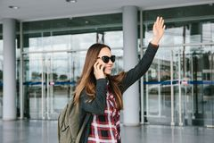 Young beautiful tourist girl at the airport or near the shopping center or the station calls a taxi or talking on a cell Royalty Free Stock Image