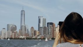 Young beautiful tourist girl taking photos of Manhattan in New York, America on smartphone from the boat on East river. stock video footage