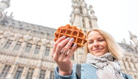 Young beautiful woman holding a traditional Belgian waffle on the background of the Great Market Square in Brussels stock photo
