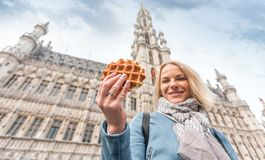 Young beautiful woman holding a traditional Belgian waffle on the background of the Great Market Square in Brussels royalty free stock photography
