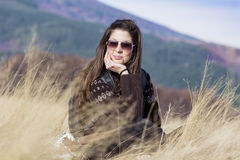 Young beautiful tourist woman sitting in a meadow with dry grass Royalty Free Stock Image