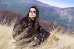 Young beautiful tourist woman sitting in a meadow with dry grass Stock Photography
