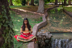 Young beautiful traditional indian woman practicing yoga in nature stock photography