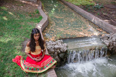 Young beautiful traditional indian woman practicing yoga in nature royalty free stock images