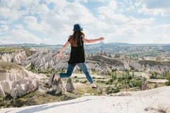 Young beautiful travel girl on top of a hill in Cappadocia, Turkey. She jumps up. Travel, success, freedom, achievement. Royalty Free Stock Image