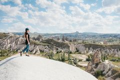 Young beautiful travel girl on top of a hill in Cappadocia, Turkey. Travel, success, freedom, achievement. Royalty Free Stock Image