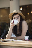 Young beautiful traveler enjoying a coffee at street cafe Royalty Free Stock Photo