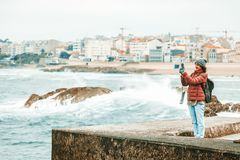 Young beautiful traveler girl with a backpack taking off the ocean and waves on a smartphone, winter, Atlantic ocean, Portugal royalty free stock image