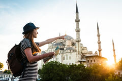 A young beautiful traveler girl in a hat with a backpack and a map next to the blue mosque is a famous sight in Istanbul Stock Images