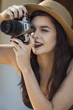 Young beautiful traveler happily taking photos with camera at ca Stock Photography