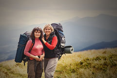 Young beautiful travelers with a backpack standing on top of the Stock Photography