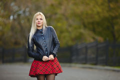 Young beautiful trendy dressed blonde woman posing outdoors against blurry foliage background looking into camera Stock Images