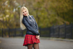 Young beautiful trendy dressed blonde woman posing outdoors against blurry foliage background smiling looking into camera Royalty Free Stock Photography