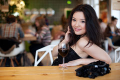 Young beautiful trendy woman in bar. Beautiful Asian girl in a p Stock Images